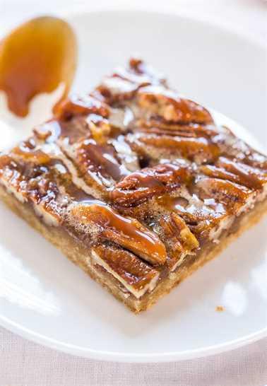 barra de pastel de nuez rociada con salsa de caramelo en un plato blanco