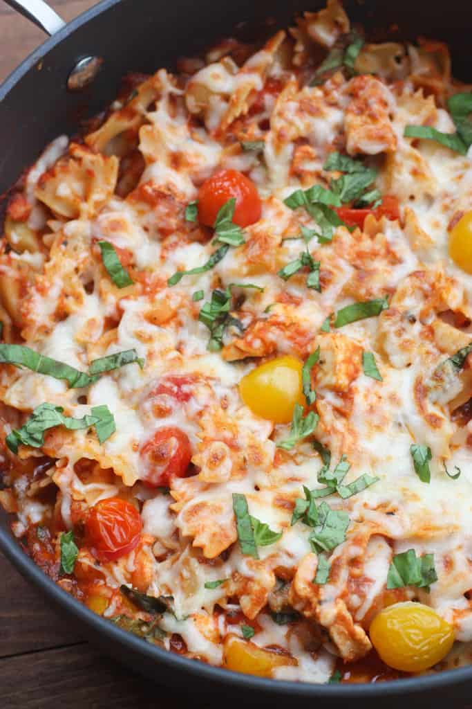 Chicken mozzarella pasta with roasted tomatoes in a pan.