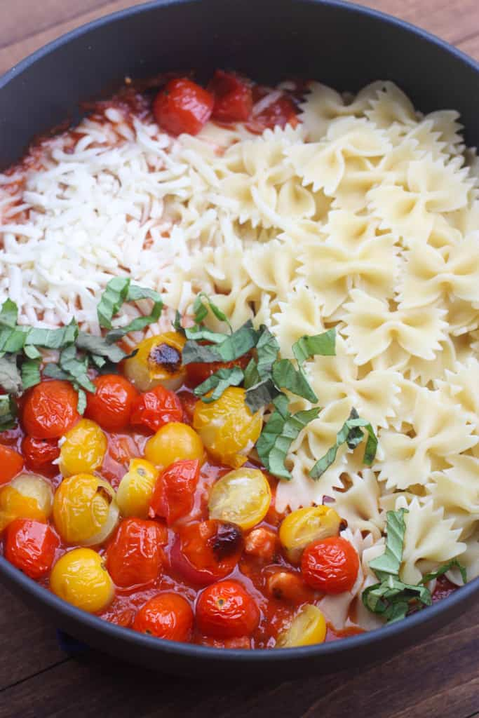 A frying pan filled with pasta, tomato, basil, and mozzarella.