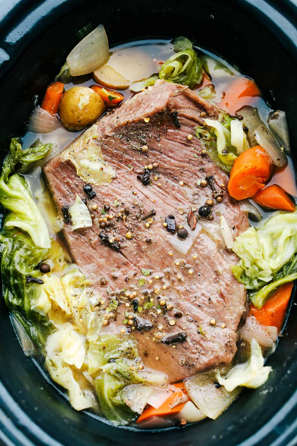 Carne de maíz en una olla de cocción lenta con repollo y zanahorias y papas picadas.