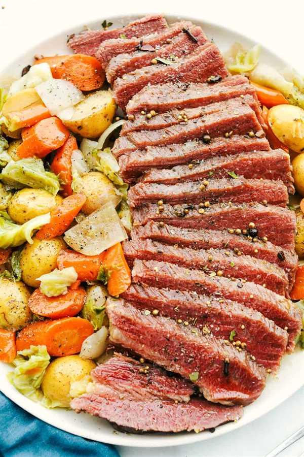 Corned beef en rodajas en una fila con papas, zanahorias y repollo a un lado.