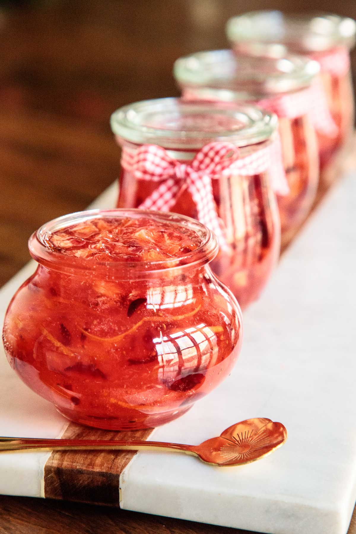 Foto vertical de mermelada de Navidad en frascos de vidrio alineados en una bandeja de mármol