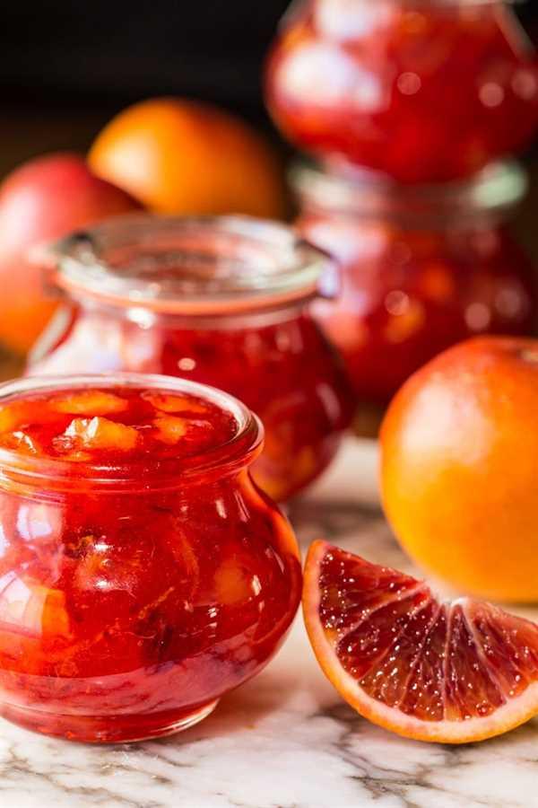 Foto de vidrio Weck frascos de mermelada de naranja de sangre fácil rodeado de naranjas de sangre.