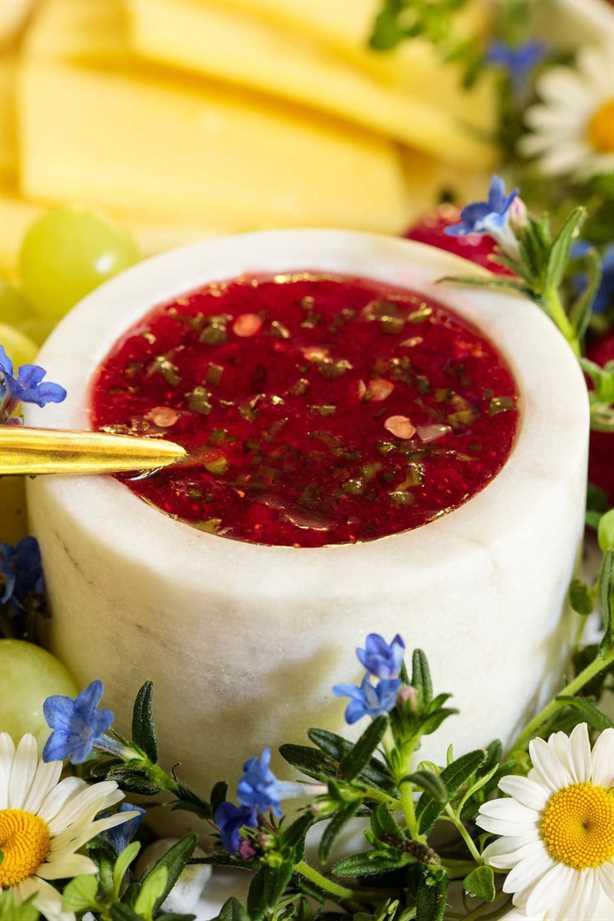 Foto vertical de mermelada de fresa y jalapeño en un pequeño frasco de mármol blanco rodeado de frutas y flores.