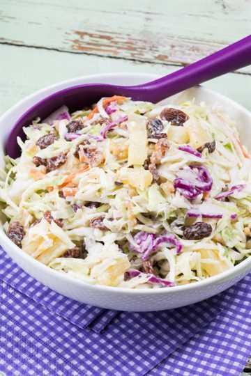 40 increíbles platos de Pascua, ensalada de col con pasas de uva y piña en un tazón con una cuchara para servir