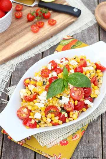 Salteado de maíz con tomate feta y albahaca en una fuente blanca