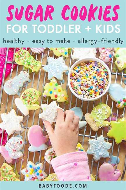 Gráfico para Post - Galletas de azúcar para niños pequeños y niños - saludable - fácil de hacer - apta para personas alérgicas con una imagen de la mano pequeña alcanzando para obtener una galleta de azúcar helada.