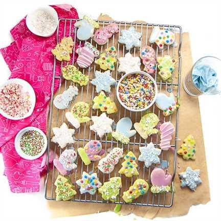 Parrilla de enfriamiento con galletas de azúcar decoradas con chispas y glaseado sin colorantes.