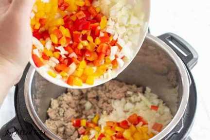 una mano vertiendo cebolla picada y pimientos en la olla instantánea