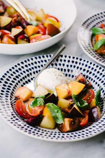 Una ensalada de frutas de hueso de verano con cerezas, duraznos, nectarinas, ciruelas, tomates, albahaca y queso burrata en un plato.