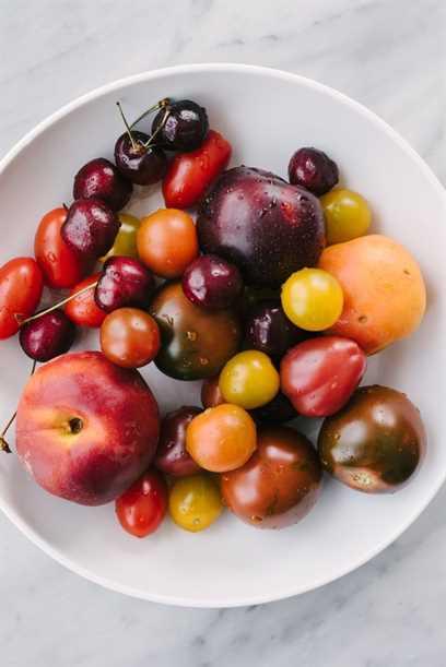 Un plato poco profundo lleno de varias frutas de hueso enteras y tomates reliquia.