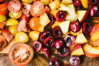 Melocotones en cubitos, nectarinas, peras, ciruelas, cerezas y tomates en una tabla de cortar para ensalada de frutas con hueso.