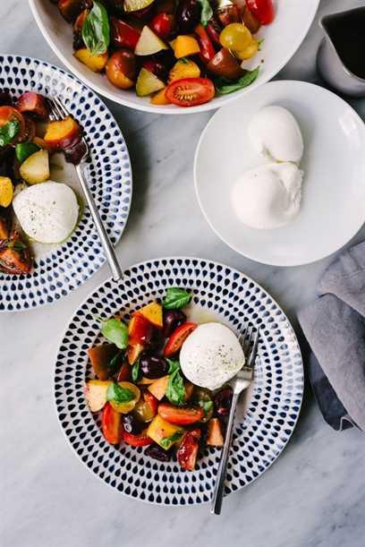Dos platos de ensalada de frutas con hueso con tomates y queso burrata sobre una mesa de mármol.