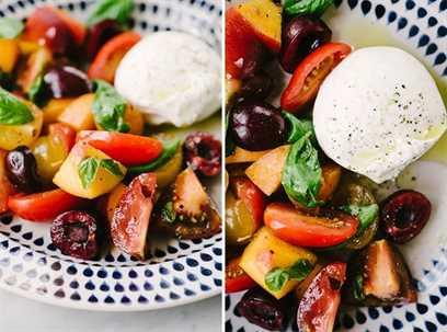 Cerrar imágenes de ensalada de fruta de hueso con ciruelas, duraznos, nectarinas, cerezas y tomates de la herencia con albahaca y una porción de queso burrata.