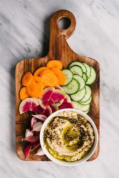 Un tazón de hummus de coliflor asado sobre una tabla para cortar madera con rábanos en rodajas, zanahorias y hummus para mojar.
