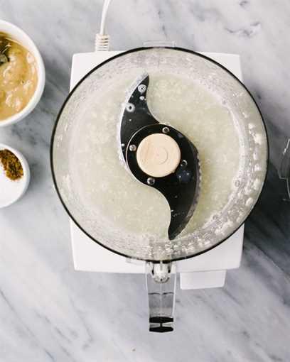 Cómo hacer hummus de coliflor. Dientes de ajo procesados con jugo de limón en el recipiente de un procesador de alimentos en una mesa de mármol.