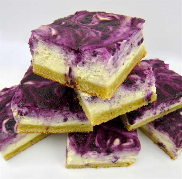 barras de pastel de queso de arándanos apilados en un plato blanco