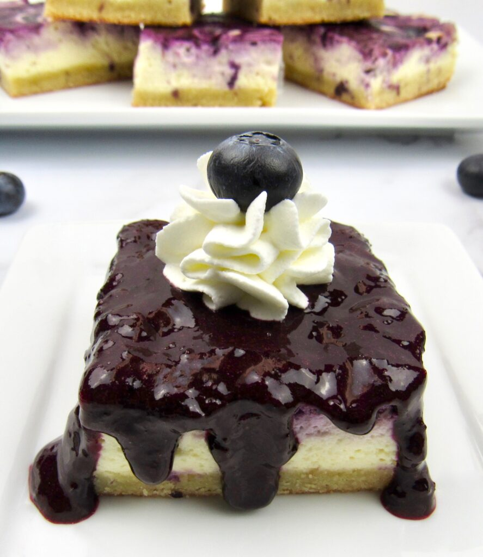 barras de pastel de queso de arándanos con salsa de arándanos y crema batida en la parte superior