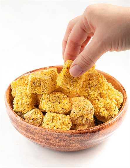 Tofu crujiente en un tazón con una mano tomando un pedazo