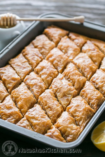 La baklava casera se muestra en rodajas en una bandeja para hornear rociada con miel de limón caliente para la mejor receta de baklava