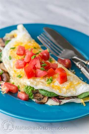 Esta tortilla de clara de huevo esponjosa está cargada de tocino, champiñones, queso y espinacas frescas que se ablandan perfectamente dentro de la tortilla. Tan satisfactorio! El | NatashasKitchen.com