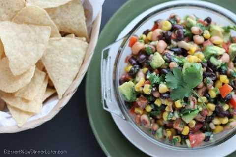 Cowboy Caviar es una salsa gruesa tipo salsa con frijoles, aguacate, tomates, maíz y un aderezo picante. ¡Ideal para picnics, comidas compartidas, fiestas o un refrigerio de un día de juego!