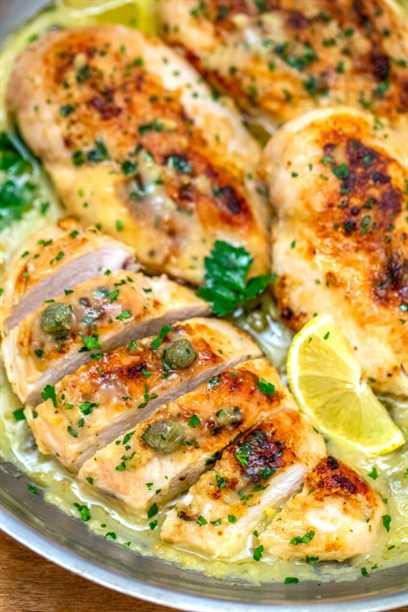 imagen de pechugas de pollo picadas en rodajas adornadas con rodajas de limón y perejil
