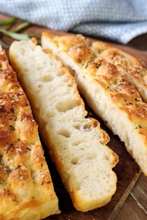 Foto del primer de las rebanadas de pan ridículamente fácil de Focaccia en una tabla de cortar de madera.