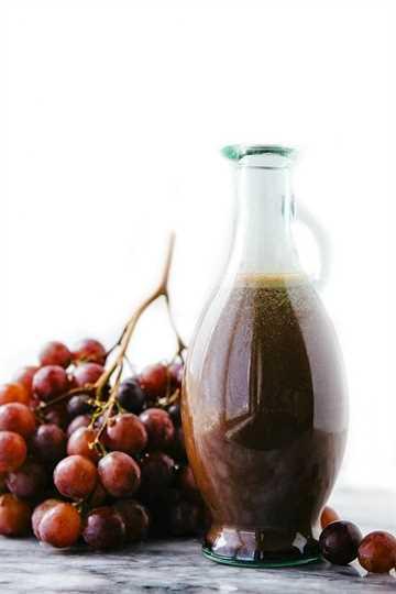 Imagen del aderezo para ensalada en el recipiente con uvas frescas en el costado