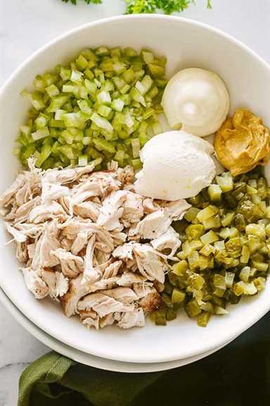 Encurtidos de eneldo, pollo desmenuzado, apio y aderezo de mayonesa dentro de una ensaladera.