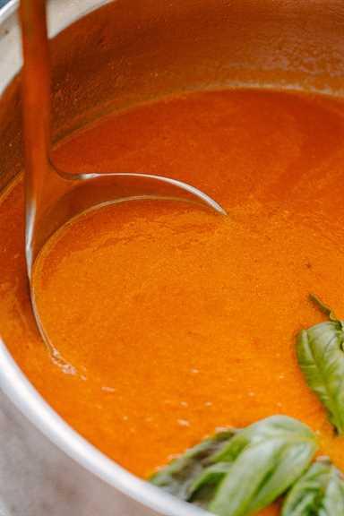 """Cucharón dentro de la olla con sopa de tomate. """"Width ="""" 640 """"height ="""" 960 """"data-pin-description ="""" Sopa de tomate asada - Sopa de tomate rica, audaz y sabrosa hecha con tomates cherry asados, ajo y albahaca. Preparada con solo un puñado de ingredientes, esta receta de sopa de tomate es mucho mejor que la versión enlatada y ¡no podría ser más simple de hacer!"""