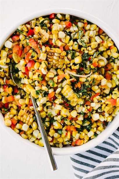 Un plato de ensalada de verano de maíz dulce a la parrilla con pimiento rojo, albahaca, cebolla verde y aderezo de lima y miel.