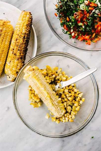 Una mazorca de maíz con granos cortados de la mazorca en un recipiente de vidrio sobre una mesa de mármol.