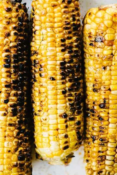 Tres mazorcas de maíz dulce carbonizado y a la parrilla.
