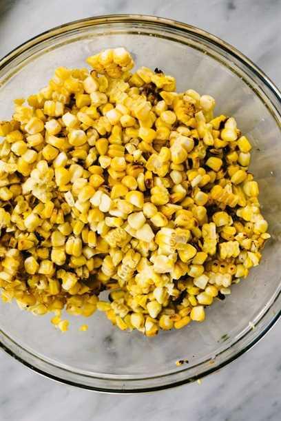 Un tazón de granos de maíz frescos a la parrilla cortados de la mazorca en una mesa de mármol.