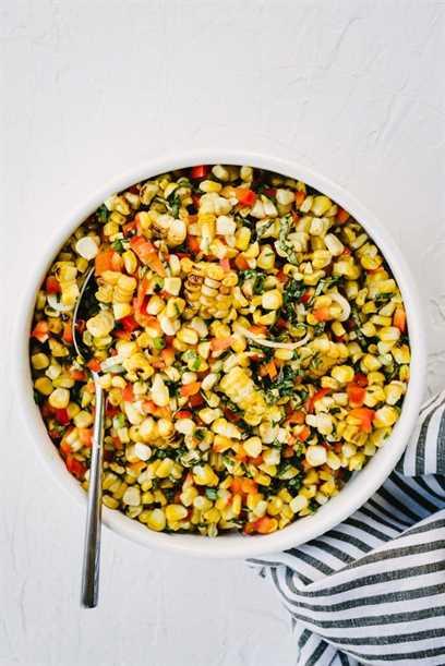 Un plato de simple ensalada de maíz a la parrilla con lima, pimiento, cebolla verde y albahaca sobre una mesa de mármol con una servilleta de rayas grises y blancas.