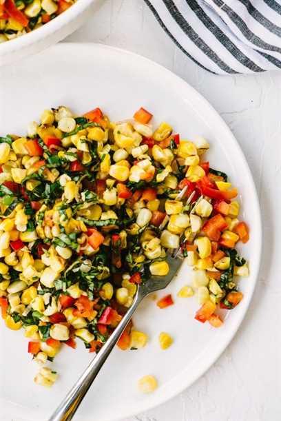 Un plato con una porción de ensalada de maíz a la parrilla con albahaca, pimientos y aderezo de lima.