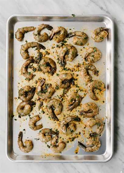 Camarones picantes arrojados con adobo en una sola capa sobre una bandeja para hornear, listos para asar.