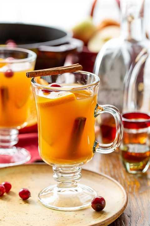 Una taza de sidra de manzana picante con ron, canela y gajos de naranja