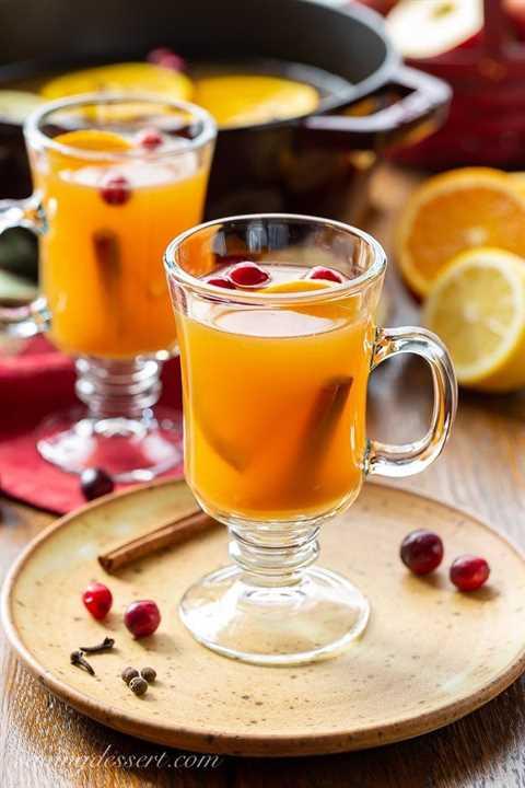 Tazas de sidra de manzana picante con canela y gajos de naranja