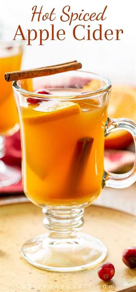 Una taza transparente de sidra de manzana picante con naranjas, arándanos y canela