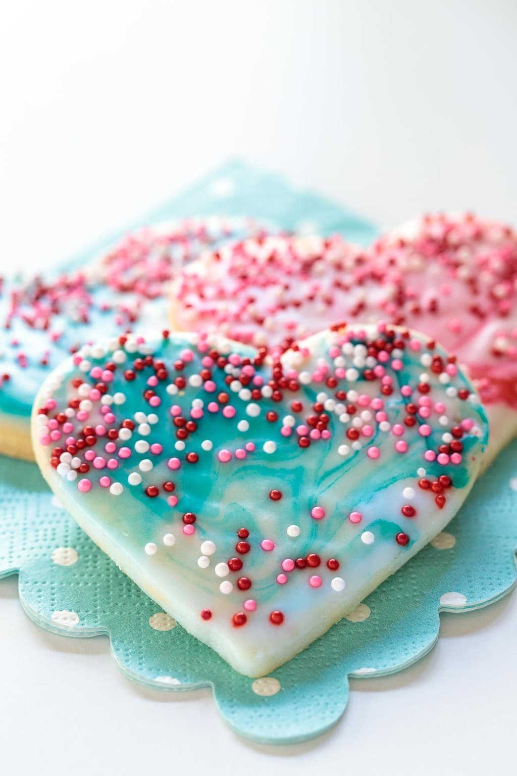 Foto aérea de Easy Decorated Valentine's Cookies en una servilleta turquesa punteada.