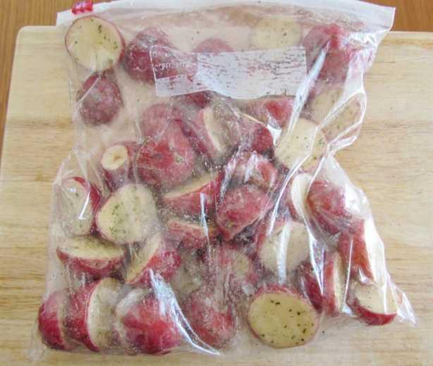 papas completamente cubiertas con aceite y mezcla de aderezo ranch en una bolsa con cierre de cremallera en una tabla de cortar