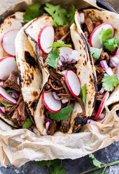 Dulce y picante Ancho Chile Tacos cortos de costilla cubiertos con rábanos y cilantro.