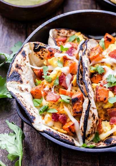 Tacos de desayuno de batata, tocino y huevo cubiertos con queso en una sartén de hierro fundido.