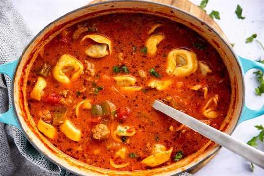 Vista de arriba hacia abajo en una olla ovalada de hierro fundido con sopa de tortellini