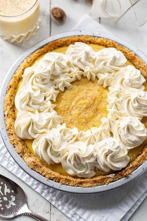 Una tarta de ponche de huevo con costra de galleta triturada cubierta con remolinos de crema batida y nuez moscada rallada fresca