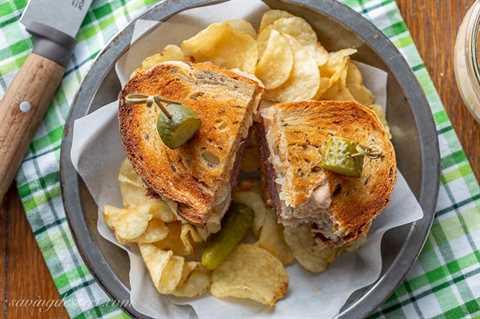 Un sándwich Reuben tostado y en rodajas con papas fritas y encurtidos