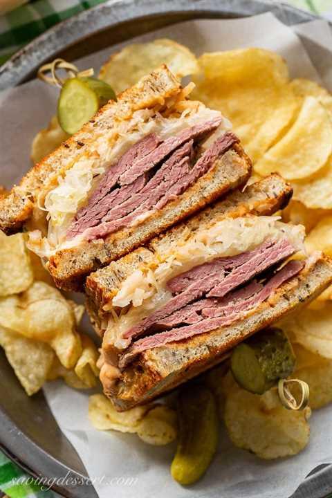 Un sándwich Reuben en rodajas servido con papas fritas y encurtidos