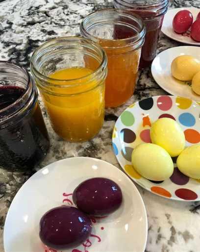 Tarros de tinte y huevos teñidos en platos